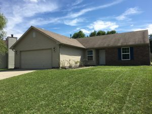 Rental house sitting on a lawn with driveway on the left. Garage on left and it's a one floor house with brown color.