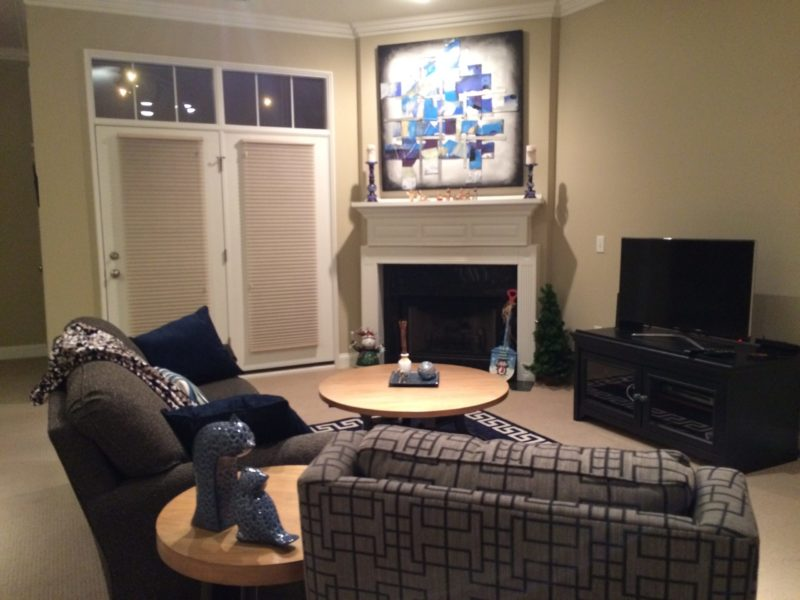 Living room of a downtown condo. Fireplace in corner next to french doors leading to patio. Painting is above fireplace. Sofa flanking the fireplace and a tv with entertainment stand.