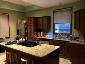 Kitchen view with granite island and stovetop. End of wall has a window over granite countertop and fridge on left side.