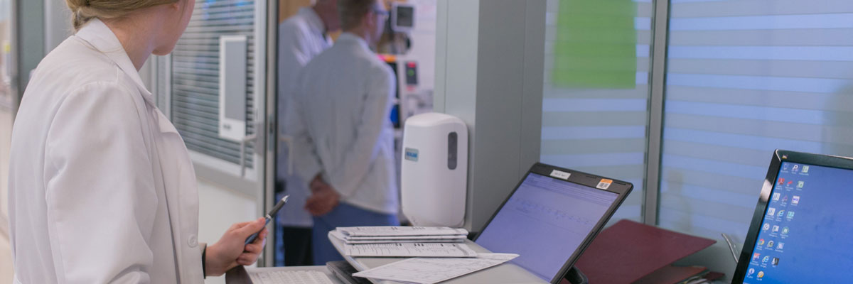 A student standing at a medical record laptop while watching two doctors converse with a patient at a distance.'