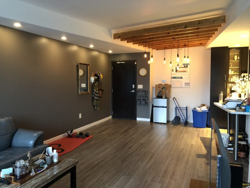 View of living room with door on one end. Kitchen is on the right. The floor is hardwood and there's a sofa on the left. On the ceiling there's a group of wood beams and lights hanging below
